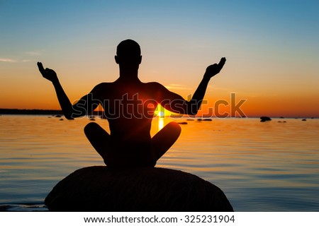 Meditating man silhouette on vibrant sunset background. Multicolored summertime horizontal outdoors image. View from backside. - stock photo