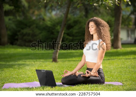 Meditating sporty young woman with laptop. Green grass background  - stock photo