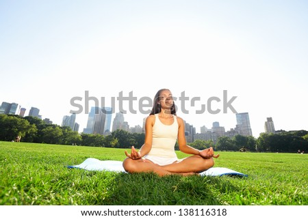 Meditating woman in meditation in New York City Central Park in yoga pose. Girl relaxing with serene relaxed expression outside in summer. Beautiful young mixed race Asian Caucasian female model. - stock photo