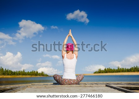 meditation and yoga practicing near the lake - stock photo