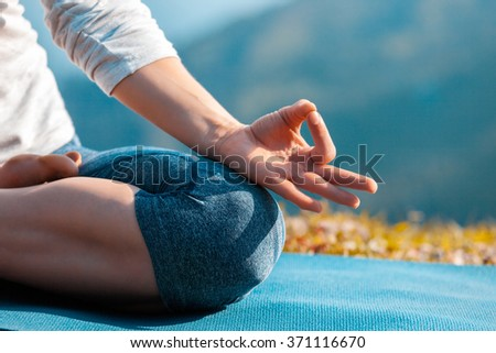 Meditation healthy life exercise concept - Close up of woman in Padmasana yoga lotus pose with chin mudra outdoors with copyspace. Teal orange color grading - stock photo