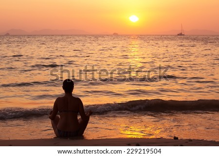 Meditation - Meditating yoga woman at at serene beach sunset. Girl relaxing in lotus pose in calm zen moment in the ocean water during yoga holidays resort retreat. Multiracial girl. - stock photo