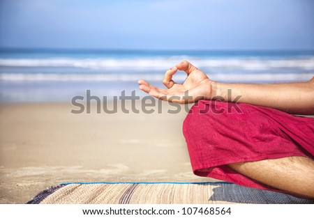 Meditation mudra of man in red trousers on the beach at ocean background - stock photo