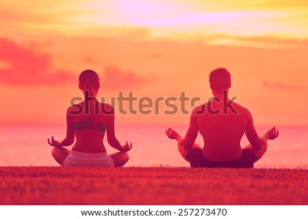 Meditation yoga couple meditating at serene beach sunset. Girl and man relaxing in lotus pose in calm zen moment in the ocean during yoga holiday class at resort retreat. - stock photo