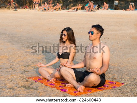 Meditation yoga couple meditating at serene beach sunset,Girl and man relaxing in lotus pose in calm zen moment  during yoga holiday ,A young couple sitting on the beach in the lotus position ,
