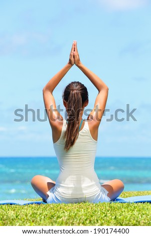 Meditation yoga woman meditating at beach relaxing in yoga pose. Serene relaxed female yoga instructor in calm nature sea scene. - stock photo