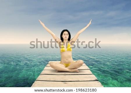 Meditation - Yoga woman meditating at serene beach - stock photo