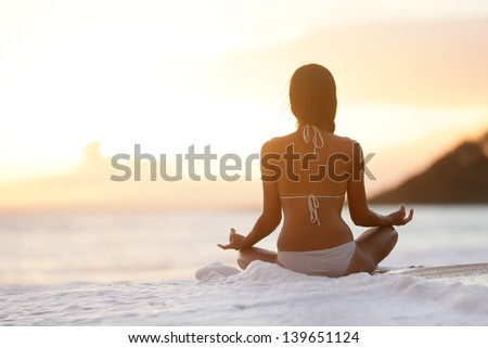 Meditation - Yoga woman meditating at serene beach sunset. Girl relaxing in lotus pose in calm zen moment in the ocean water during yoga holidays resort retreat. Multiracial girl. - stock photo