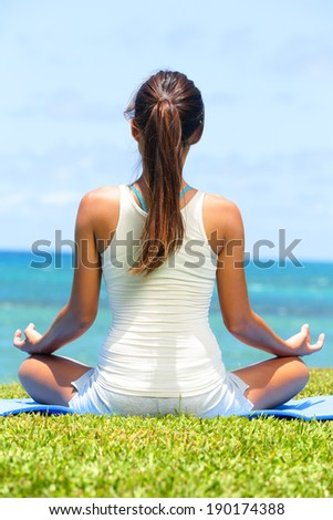 Meditation yoga woman on beach meditating by ocean sea sitting in lotus position with back turned serene and happy. Asian girl sitting relaxing enjoying summer beach. - stock photo