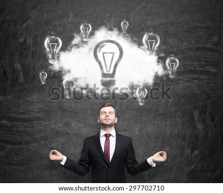Meditative businessman at the cloud with light bulbs as a concept of the new business ideas. Black chalk board as a background. - stock photo
