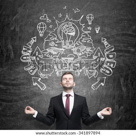 Meditative businessman is dreaming about an invention of new business ideas for business development. Business plan and idea sketch is drawn on the black chalkboard. - stock photo