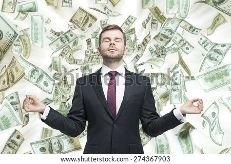 Meditative young businessman. Dollars notes are falling down from the ceiling. A concept of career success.