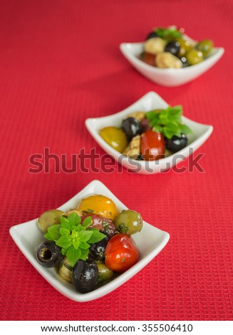 Mediterranean antipasti salad with mozzarella balls, green and black olives and cherry tomatoes and some tiny-leafed basil.