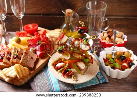 mediterranean appetizers and antipasti with olives,mozzarella,dried tomatoes on wooden table - stock photo