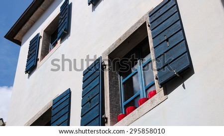 Mediterranean Architecture. Rustic windows with blue shutters on white house. - stock photo