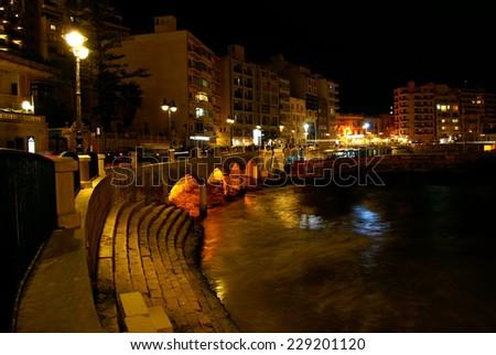 MEDITERRANEAN COAST, ST.JULIANS BAY , MALTA ISLAND - NOVEMBER 2, 2014. Autumn night on the mediterranean coast in Malta - stock photo