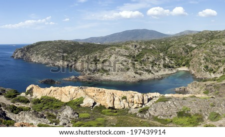 mediterranean desert beach with beautiful blue water color, and mountains in the background, at natural park of cape of creus - stock photo