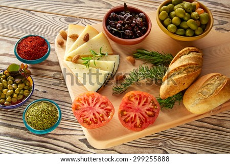 Mediterranean food bread oil olives cheese spices peppers garlic almods rosemary - stock photo