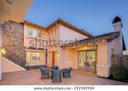 Mediterranean home exterior with seating arrangement in light orange at night with stone wall and staircase. - stock photo