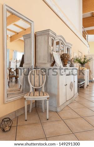 Mediterranean interior - a stripped chair by a big mirror - stock photo