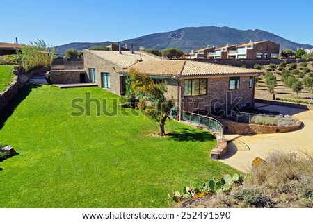 Mediterranean landscape with holiday villa, lawn and blue sky background, Cadaques village, Catalonia, Costa Brava, Spain - stock photo