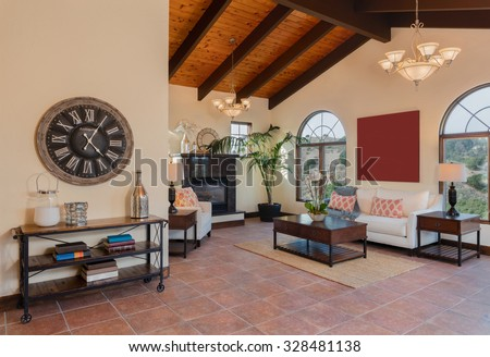 Mediterranean living room in beige with sofa, wooden stands, fireplace place, coffee table, huge clock and wooden ceiling. - stock photo