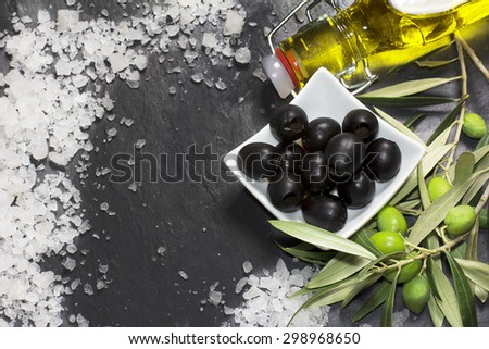 Mediterranean olives with virgin extra oil on black background - stock photo