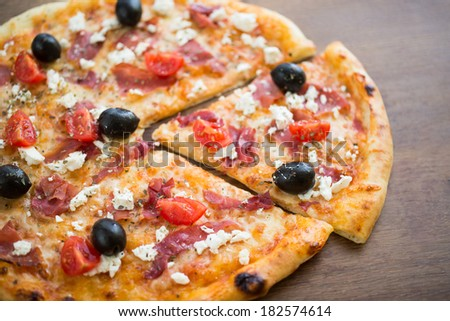 Mediterranean Pizza Slice - Mediterranean pizza with black olives, cherry tomatoes, ham and cottage cheese on a wooden table. Top view. - stock photo