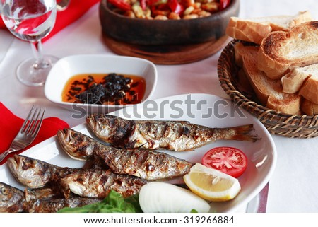 Mediterranean restaurant. Plate with fried fish and vegetables near bread - stock photo