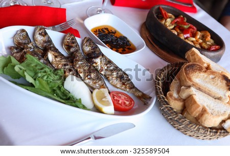 Mediterranean restaurant. Plate with fried fish and vegetables near bread