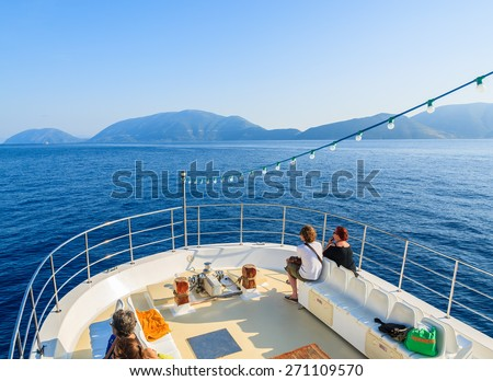 MEDITERRANEAN SEA, GREECE - SEP 19, 2014: tourists on deck of a boat sailing on blue sea. Daily cruise trips take place from Kefalonia island to Ithaka island in summer time. - stock photo