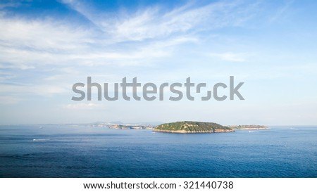 Mediterranean sea landscape with Procida island under cloudy sky, view from Ischia Ponte  - stock photo