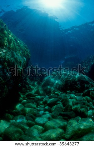 Mediterranean seabed, in the background the sun's rays - stock photo
