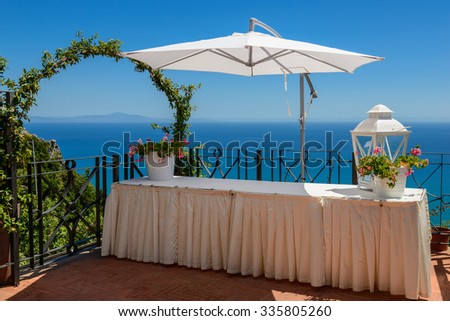 Mediterranean seascape with a table and sun-shade at the foreground, Amalfi coast, Italy.