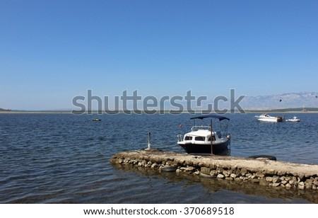 Mediterranean seaside view with small handmade pier and boats with mountains on the horizon. Fishermen boats in Mediterranean sea. Blue fishing boat bonded to limestone brickwork handmade pier. - stock photo