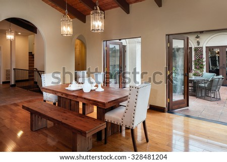 Mediterranean Spanish style wooden kitchen with huge breakfast table leading to outdoors / patio. Kitchen Interior Design Architecture. - stock photo