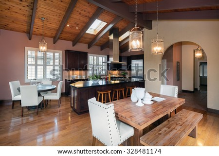Mediterranean Spanish style wooden kitchen with huge kitchen island, wooden dining table and bar chairs / stools. Kitchen Interior Design Architecture. - stock photo