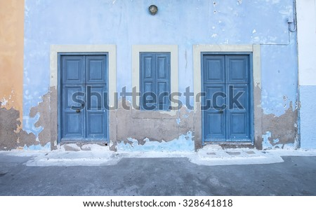 Mediterranean style exterior. Blue wooden doors and window shutters on old painted wall on a Greek island of Kastelorizo - stock photo