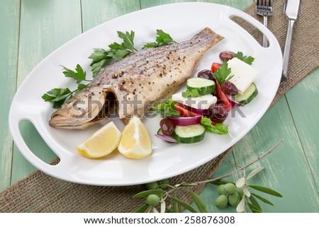 Mediterranean style organic roasted whole sea bass, garnished with Greek salad. - stock photo