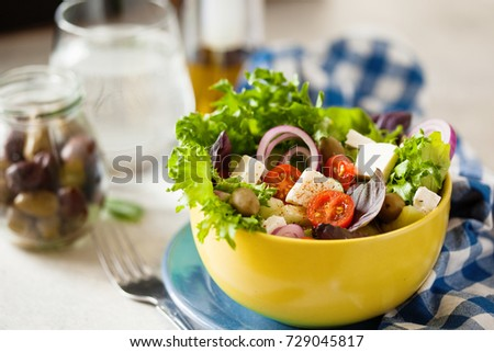 Mediterranean style salad with feta, mixed greens, cucumber, cherry tomato and green olives in bowl, selective focus