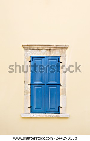Mediterranean style window. Blue on yellow wall with closed shutters - stock photo