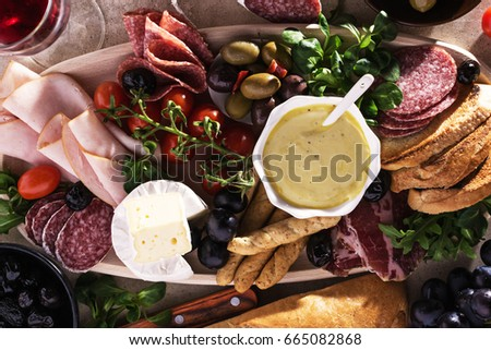 Mediterranean variety food ingredients  with ham, salami, baked olives, bread sticks,brie,tomatoes  for snacks served on a wooden board