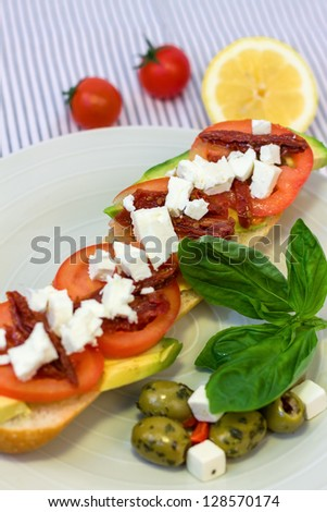 Mediterranean vegetable sandwich with tomatoes, avocado, feta cheese and basil - stock photo
