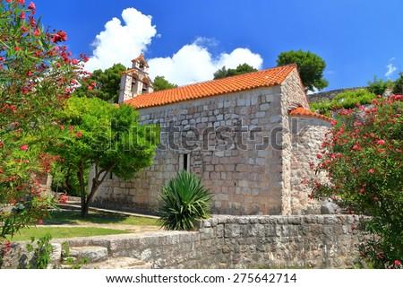 Mediterranean vegetation provide shadow on traditional stone church, Montenegro - stock photo