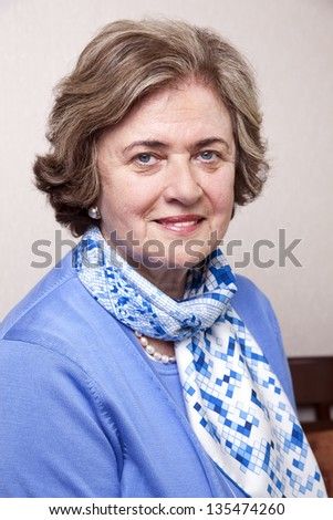 Medium close-up portrait of an elegant amd well maintained senior woman (in her late 60's) smiling a toothy smile to the camera. - stock photo