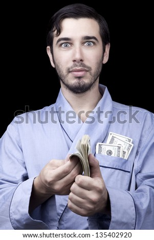 Medium closeup of an adult man (30 years old). He's looking at the camera with an awed & surprised expression, fluttering stack of 100 US$ bills in his hands. Isolated on black background. - stock photo