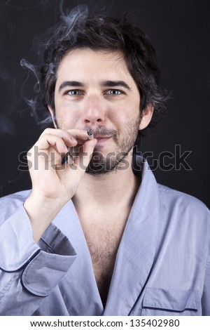 Medium closeup of an adult man (30 years old), which  appears to be quite a bum, staring at the camera with a satisfied look while smoking a marijuana spliff (aka reefer; joint). Dark gray background. - stock photo