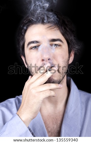 Medium closeup of an adult man (30 years), which  appears to be quite a bum, giving the camera a numb gaze, concentrated in smoking a marijuana spliff (aka reefer; joint). Isolated on black background - stock photo