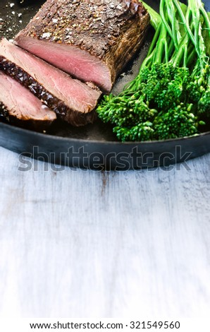 Medium cooked steak on a cast iron pan with fresh green vegetables   - stock photo