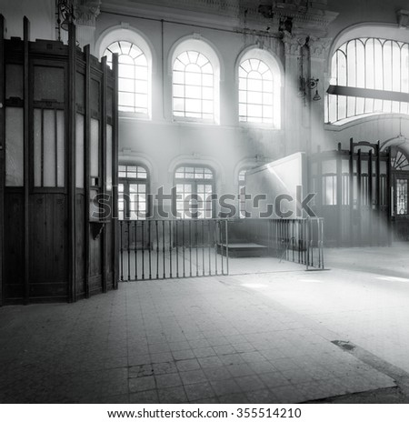 Medium format film photography shot. Black and white image of an abandoned  railway station lobby with a light effect through the windows - stock photo